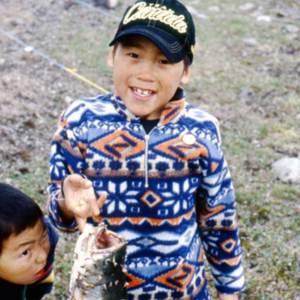 Paul I. (7 ans) exhibant fièrement un omble chevalier (Salvelinus alpinus) qu'il vient de pêcher (Nunavut)