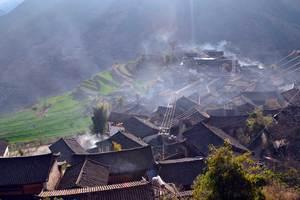 Les volutes de fumée des chel shul (petits tas de branchages de pin et d'azalées enflammés) éliminent les impuretés dans le village naxi au matin du Sacrifice au Ciel (Wumu)